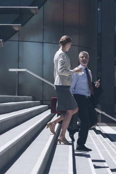 Ein Anwalt und eine Anwältin auf einer Treppe im Gespräch