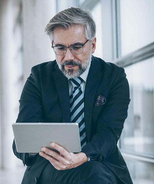 Bärtiger Mann im Anzug liest konzentriert etwas auf einem Tablet